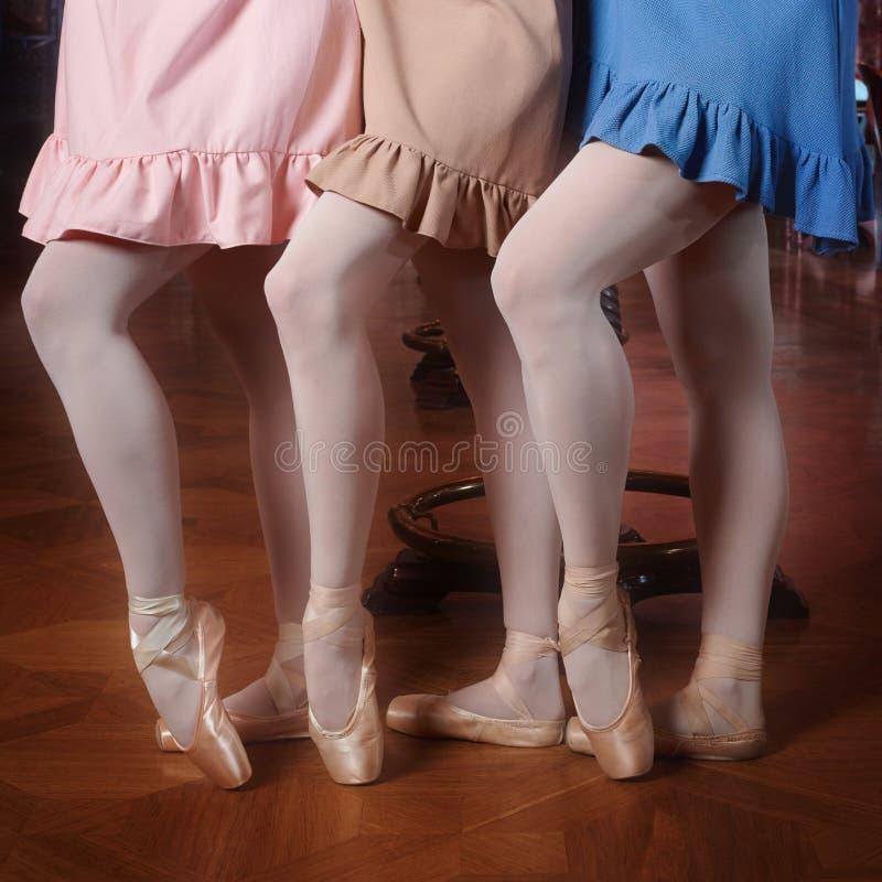 Façonnez les ballerines dans des robes colorées faisant le pas image libre de droits