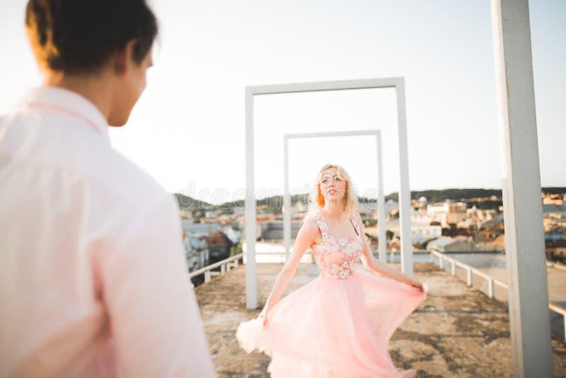 Façonnez les beaux beaux couples posant sur le toit avec le fond de ville Jeune homme et extérieur blond sensuel lifestyle image libre de droits