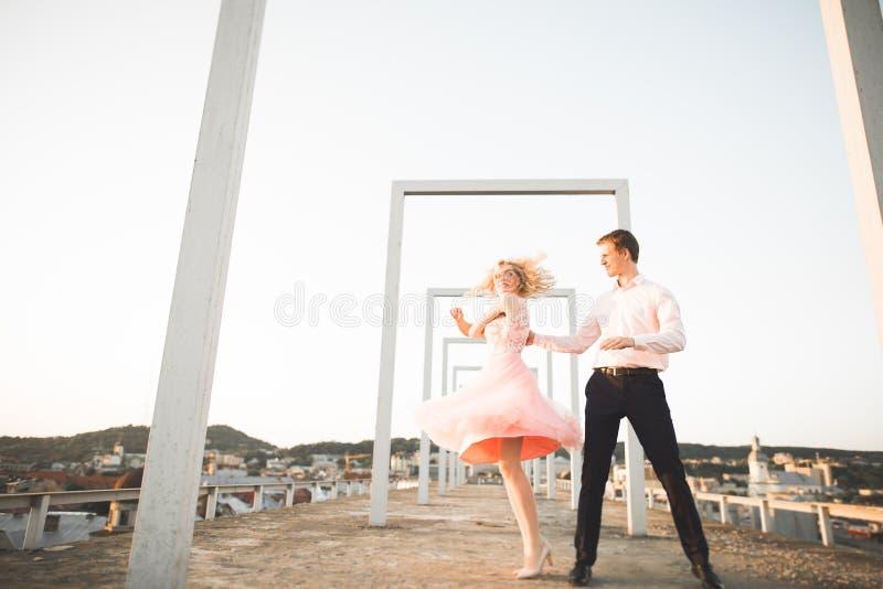 Façonnez les beaux beaux couples posant sur le toit avec le fond de ville Jeune homme et extérieur blond sensuel lifestyle photo libre de droits