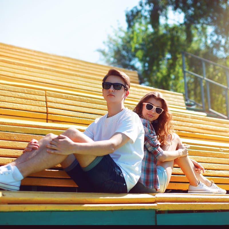 Façonnez les couples de hippie dans des lunettes de soleil se reposant sur la ville de banc images libres de droits