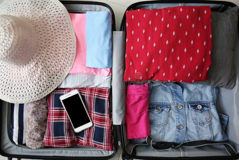 Fałdowy odziewa, słomiany kapelusz i telefon komórkowy w otwartej walizce, odgórny widok obrazy royalty free