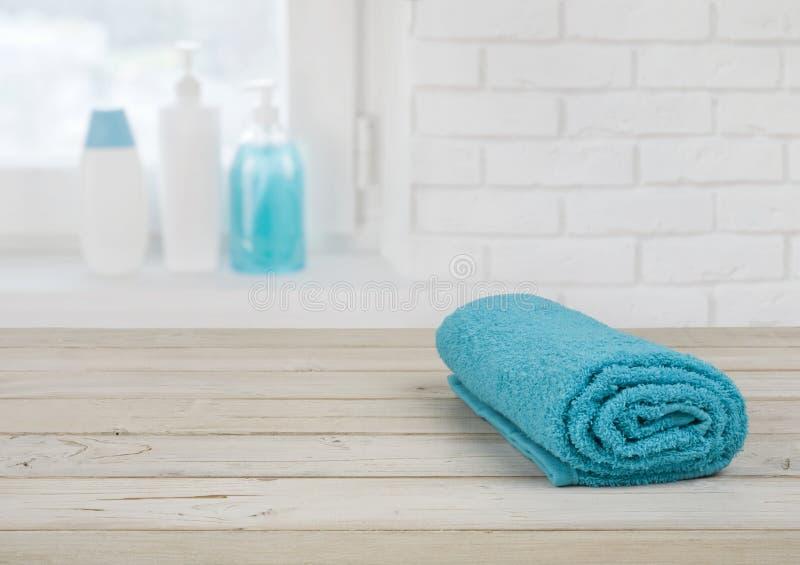 Fałdowy ręcznik na drewnianych deskach nad defocused ściana z cegieł okno zdjęcie stock