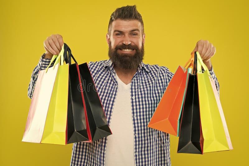 Fa?a comprando mais alegre Cara alegre do moderno farpado do homem para levar os sacos de compras de papel no fundo amarelo aprec imagens de stock royalty free