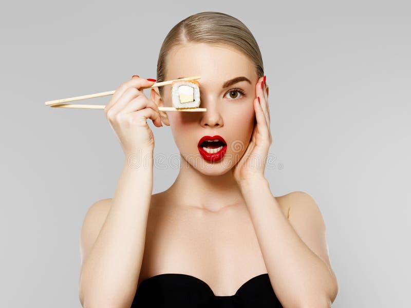 Fa?a dieta o conceito nutrition Mulher de sorriso bonita que come o rolo de sushi com hashis retrato da forma do modelo da beleza imagens de stock royalty free