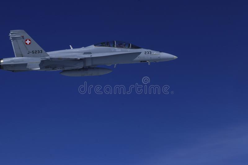 FA-18 military jets from Swiss Airforce escorting civil airplaine in the swiss alps stock photo