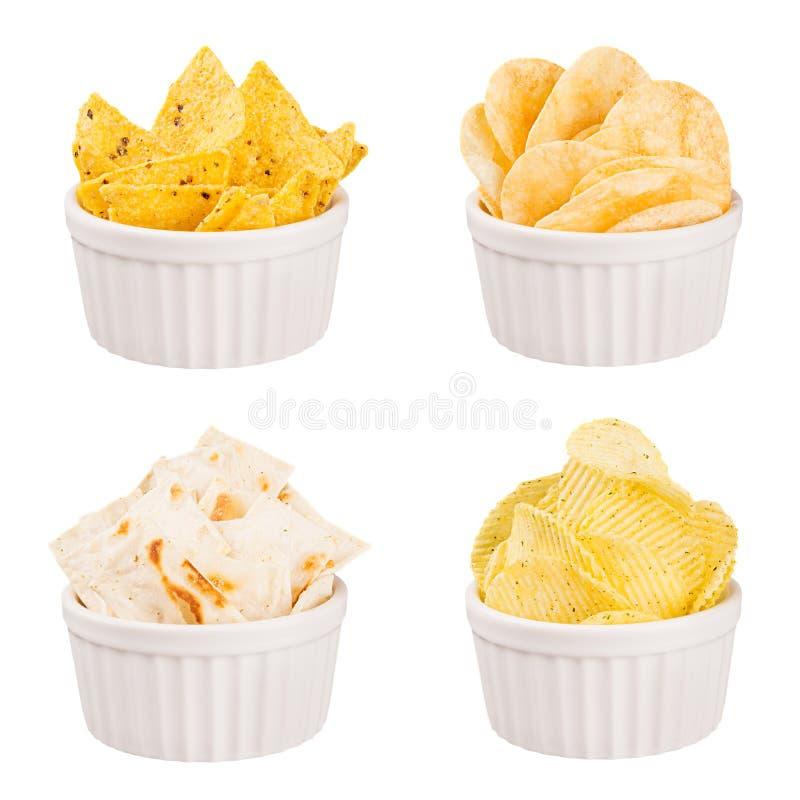 Fa un spuntino la raccolta - le patatine fritte croccanti, i nacho, tortiglia in ciotole bianche della ceramica, isolate fotografie stock