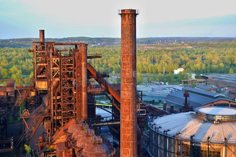 Fabbrica abbandonata delle industrie siderurgiche - camino arrugginito soleggiato dal sole immagini stock