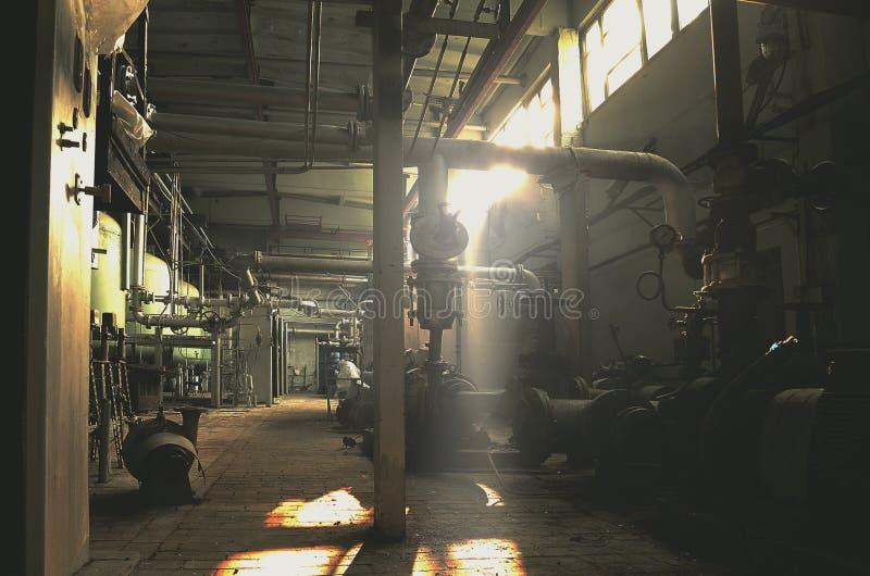 Fabbrica abbandonata e d'annata che sviluppa di mattina luce solare fotografie stock libere da diritti