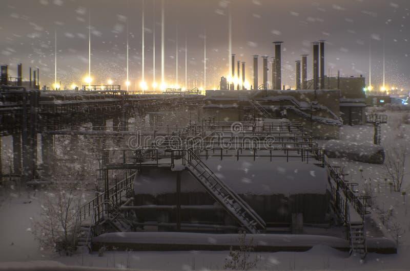 Fabbrica abbandonata, nell'inverno, con i barilotti ed i tubi sulle zone industriali d'ardore delle luci di orizzonte, paesaggio  immagine stock