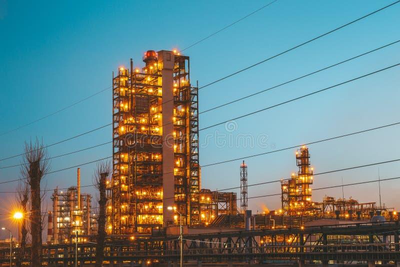 Fabbrica della raffineria dell'olio industriale o pianta con i tubi e torri petrochimica del petrolio con illuminazione di notte fotografia stock libera da diritti