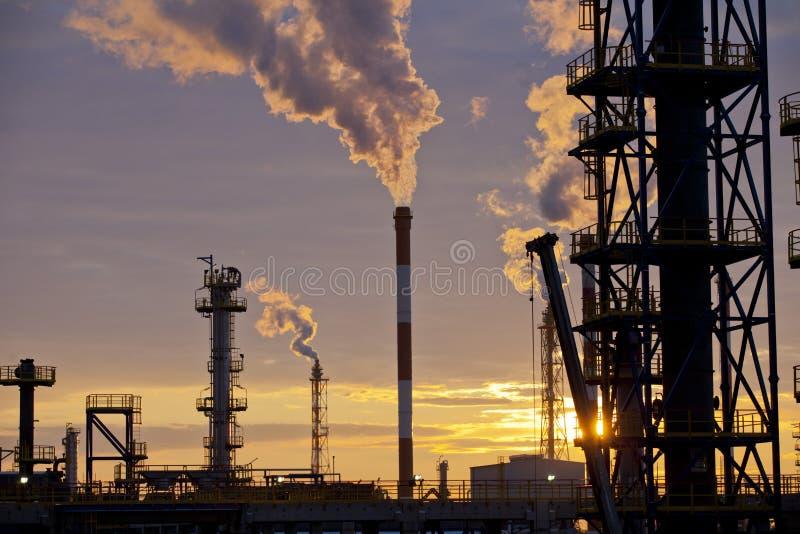 Fabbrica della raffineria di industria petrolifera al tramonto immagini stock libere da diritti