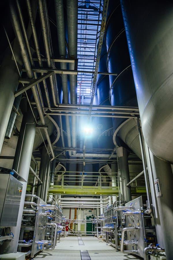 Fabbrica di birra moderna Grandi tini per fermentazione e maturazione della birra e conduttura per la consegna delle componenti fotografie stock libere da diritti