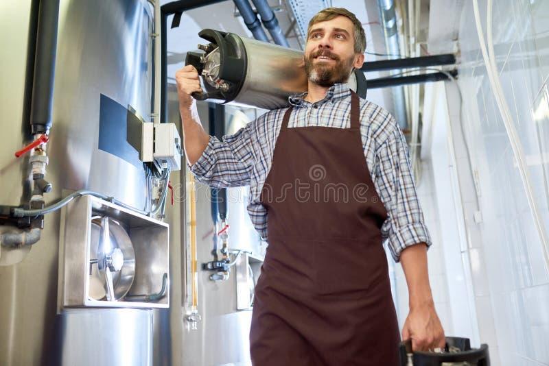 Fabbricante di birra barbuto con i barili di birra fotografia stock