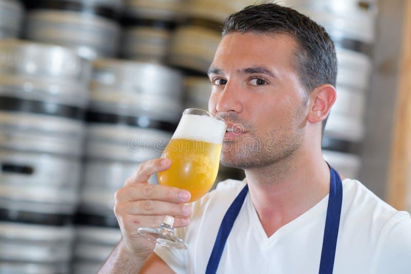 Fabbricante di birra bello in birra uniforme dell'assaggio alla fabbrica di birra fotografia stock libera da diritti