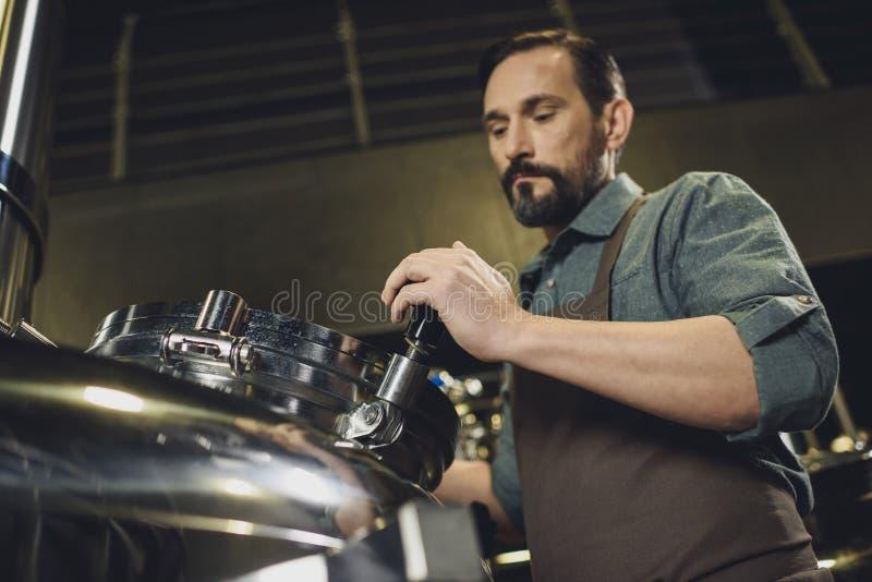 Fabbricante di birra che ispeziona carro armato fotografia stock