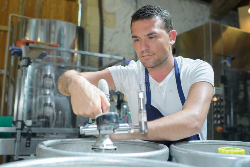 Fabbricante di birra del ritratto che lavora alla fabbrica di birra immagine stock libera da diritti
