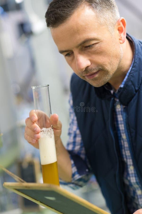 Fabbricante di birra in birra uniforme dell'assaggio alla fabbrica di birra immagine stock