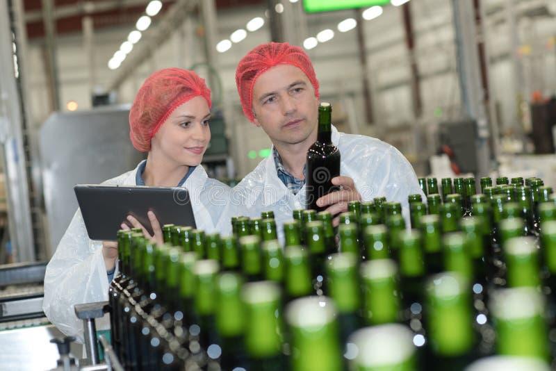 Fabbricanti di birra del ritratto che controllano le birre alla fabbrica di birra fotografia stock libera da diritti