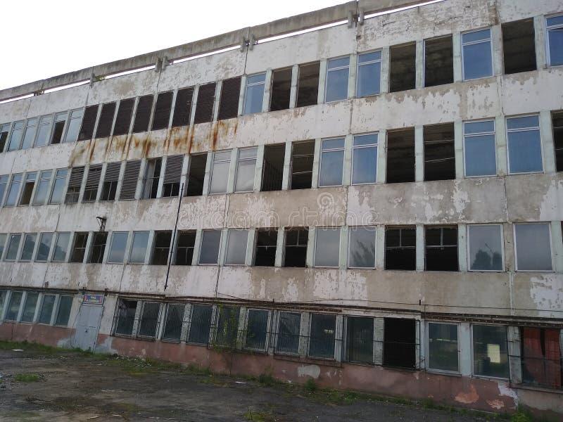 Fabbricato industriale di Distroyed con le finestre rotte grigio fotografie stock