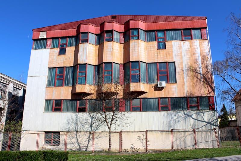 Fabbricato industriale di stile della guerra fredda grande con la facciata dilapidata dietro il recinto del metallo ed alberi sen fotografia stock libera da diritti