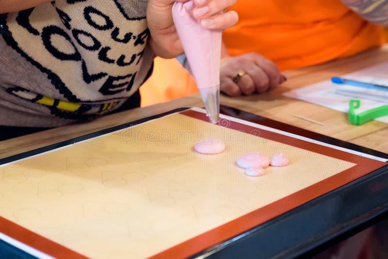 Fabbricazione dei macarons con la borsa della pasticceria immagini stock libere da diritti