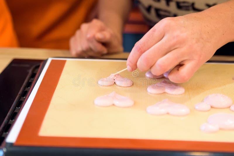 Fabbricazione dei macarons con la borsa della pasticceria immagine stock libera da diritti