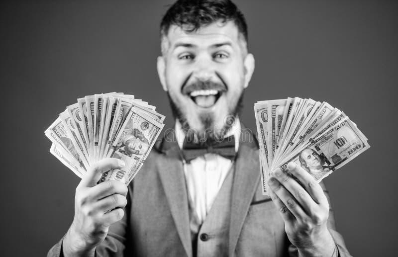 Fabbricazione dei soldi con il suo proprio affare Uomo barbuto che tiene denaro contante Uomo d'affari ricco con le banconote dei immagine stock libera da diritti