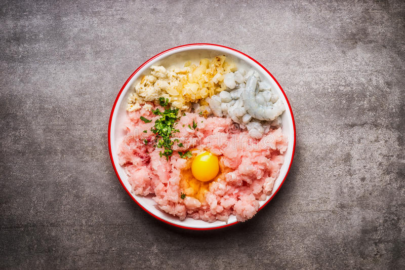 Fabbricazione dei tortini del pesce Cottura degli ingredienti in ciotola: Pesce tritato, uovo, gamberetti, cipolla e pane inzuppa fotografia stock