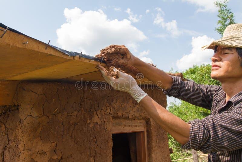 Fabbricazione del tetto della casa del fango fotografia stock libera da diritti