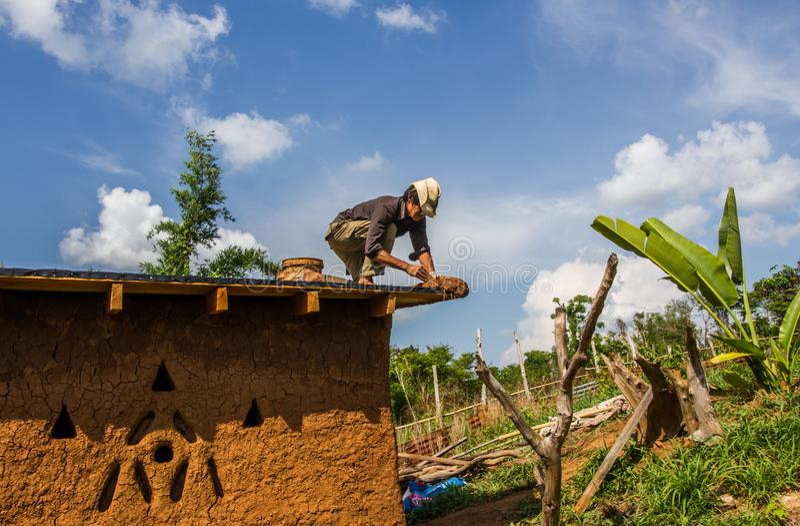 Fabbricazione del tetto della casa del fango immagini stock