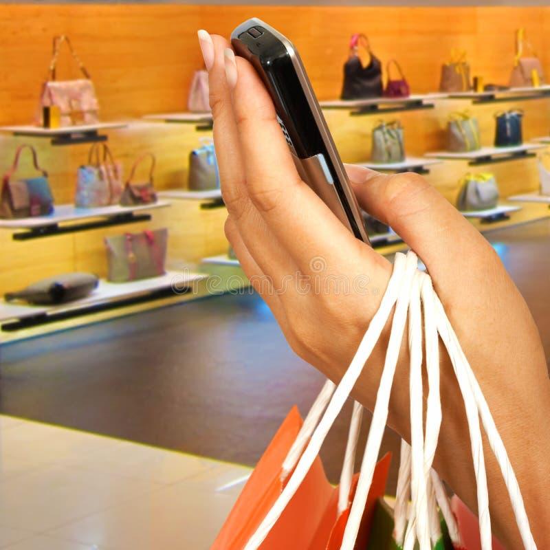 Fabbricazione della chiamata di telefono in un centro commerciale fotografia stock libera da diritti