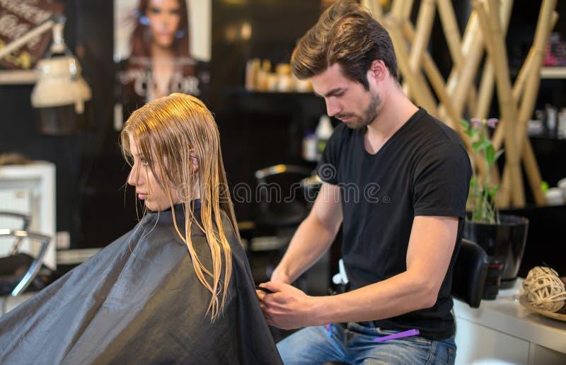 Fabbricazione dello stile di capelli nuovo per la giovane bionda fotografia stock libera da diritti