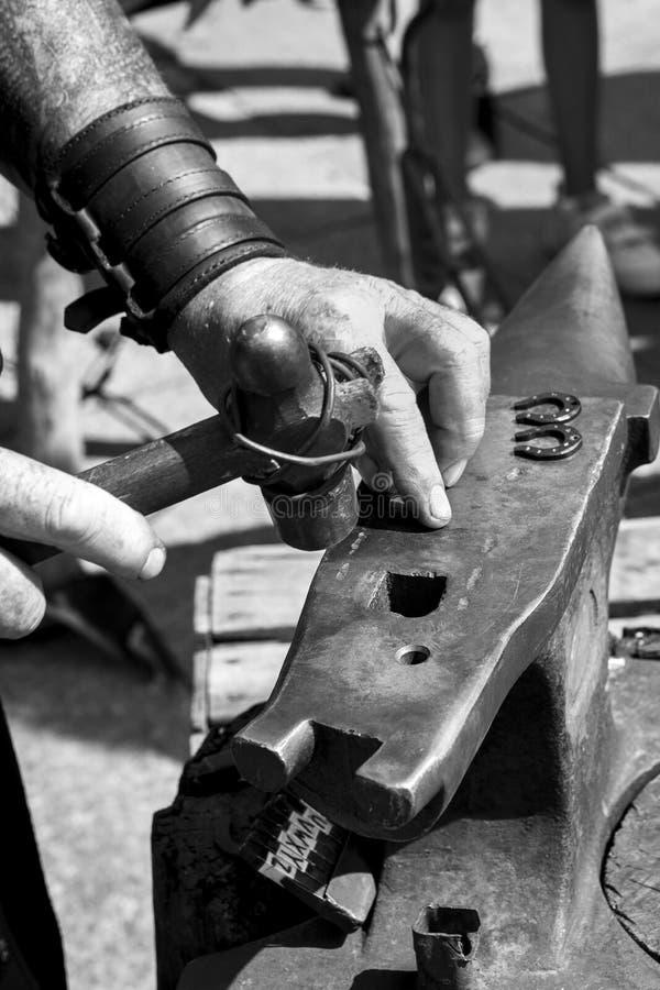 Fabbro che lavora ad una vecchia incudine accanto ai suoi strumenti sull'esterno fotografie stock