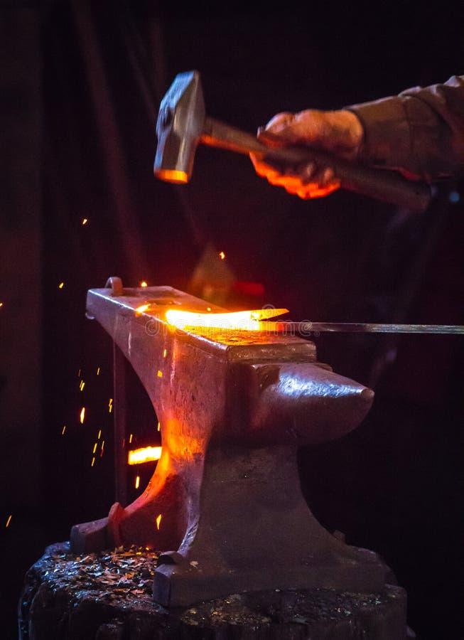 Fabbro che martella una barretta di metallo calda fotografie stock libere da diritti
