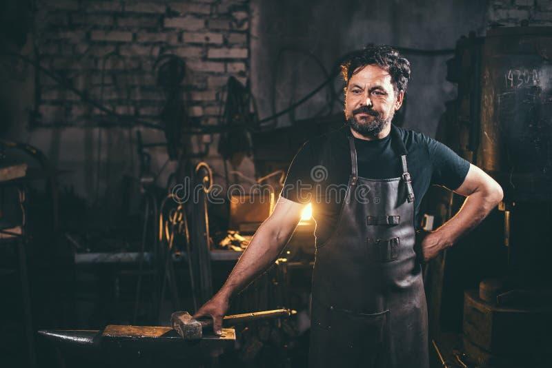 Fabbro senior in fucina fotografia stock