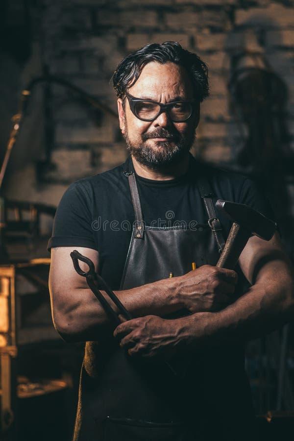 Fabbro senior in fucina fotografie stock libere da diritti