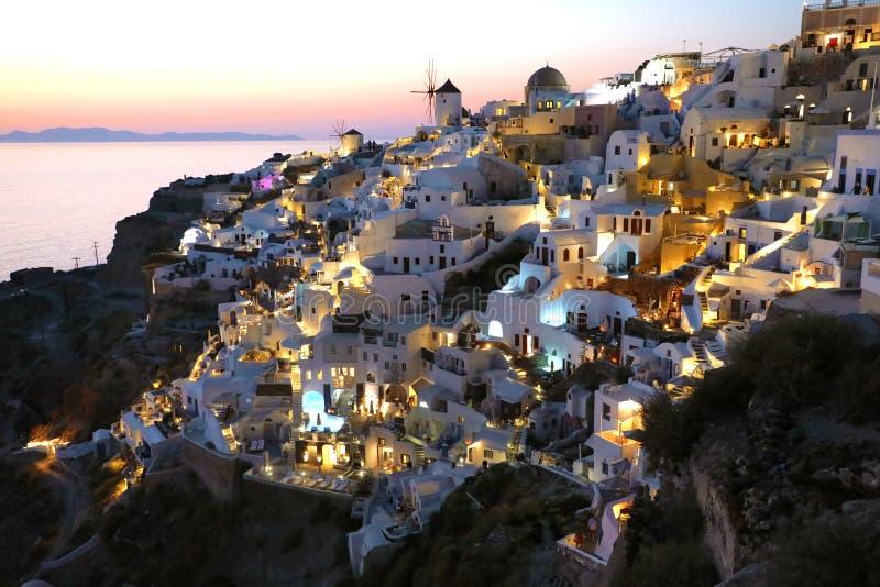 Fabelachtig schilderachtig die dorp van Oia op de rotsen met traditionele witte huizen en windmolens in Santorini-eiland bij zons stock afbeeldingen