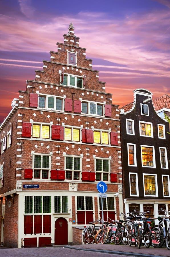 Fabelachtige oude middeleeuwse huizen met blinden bij schemer en fietsen stock foto's