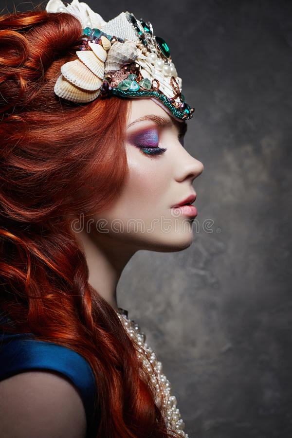 Fabelachtige roodharige het meisje kijkt, blauwe lange kleding, heldere make-up en grote wimpers Geheimzinnige feevrouw met rood  stock foto's