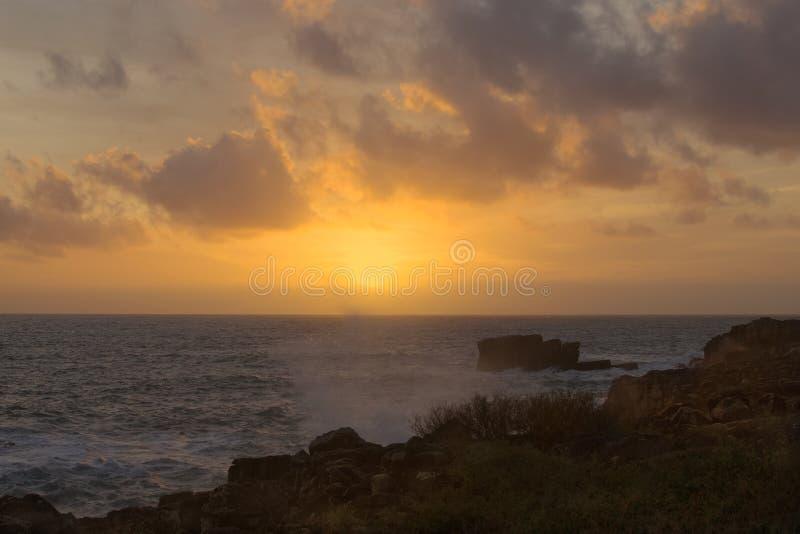 Fabelhafter Sonnenuntergang auf dem Strand Meer ist stürmisch Welle bricht auf Felsen stockfotografie