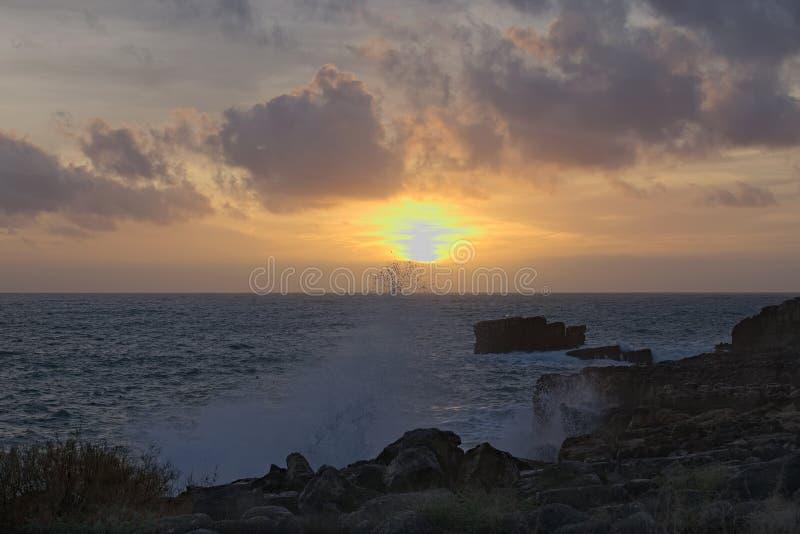 Fabelhafter Sonnenuntergang auf dem Strand Meer ist stürmisch Welle bricht auf Felsen stockbilder