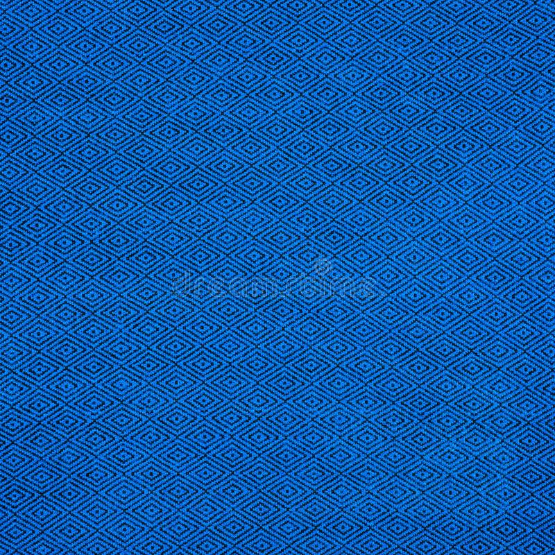 Fabric of blue color for warm autumn dress or skirt. On the fabric is a picture in the form of black rhombus royalty free stock images