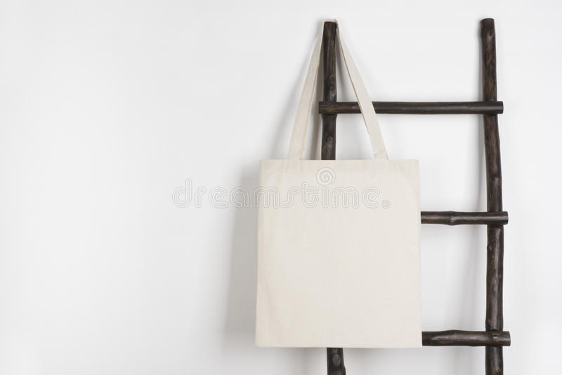 Fabric cloth shopping bag mockup hanging on vintage wooden stepladder stock photography