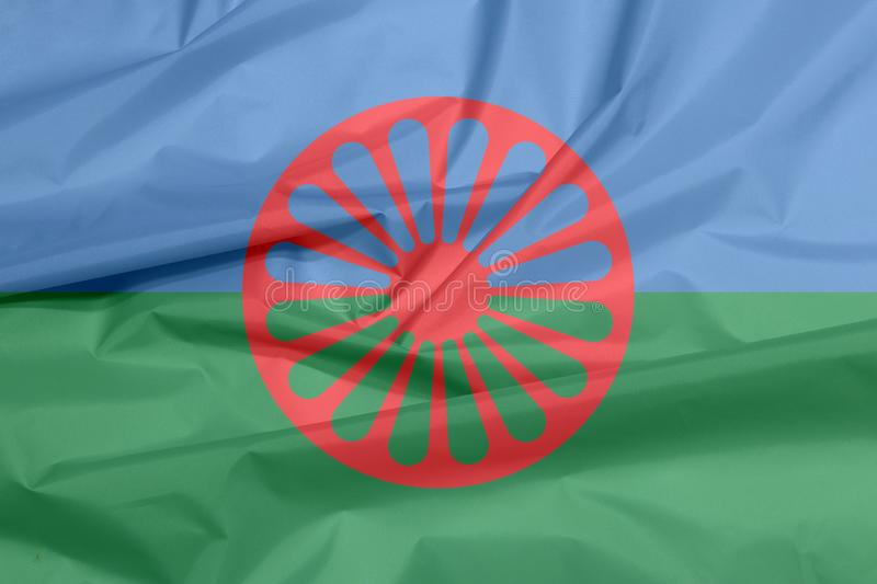 Fabric flag of Romani people. Crease of the Gypsies flag background. Fabric flag of Romani people. Crease of the Gypsies flag background, blue and green royalty free stock image