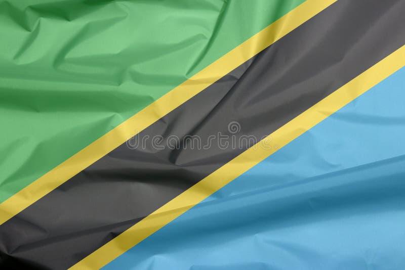Fabric flag of Tanzania. Crease of Tanzanian flag background. Fabric flag of Tanzania. Crease of Tanzanian flag background, A yellow-edged black diagonal band stock images