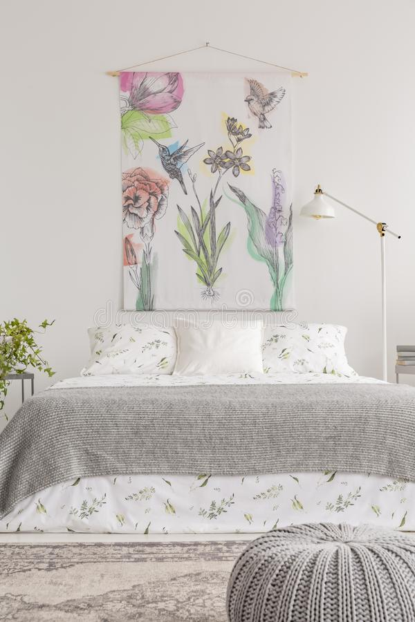 Fabric with flowers hanging on white wall in bright bedroom interior with metal lamp, double bed with floral sheets. And grey blanket in the real photo royalty free stock photo