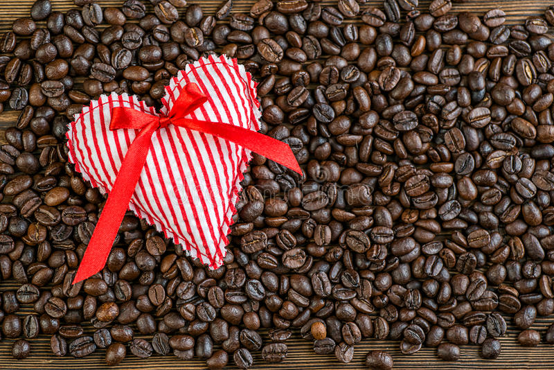Fabric heart on coffee beans, valentines day or celebrate love image stock photos