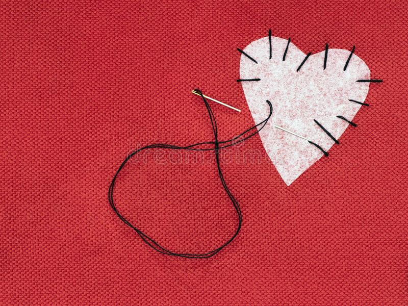 Fabric heart red with white patch and black sewing thread. Mend broken heart concept. royalty free stock photos