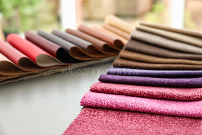 Fabric and leather samples of different colors design on table stock photos