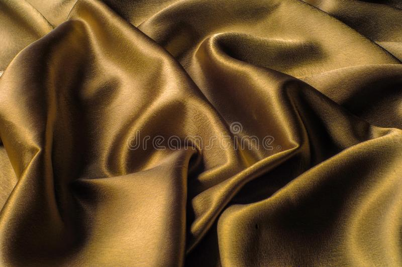 Fabric made of silk fabric metal thread metallic sheen gold. Just like looking at a stunning waterfall, this golden yellow Silk C. Harmeuse stands alone royalty free stock photo